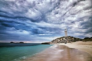 Beach and lighthouse with grey skies